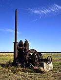 Photo of a very rusted industrial-looking pump with tall tube and wheel sits in a flat rice field.