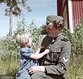 A Finnish Waffen-SS volunteer of the 5th SS Panzer Division Wiking talking with a little girl in a village in Kurkijoki, Karelian Isthmus, Finland (now Russia) 10 June 1943. (45898812575).jpg