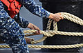 A U.S. Navy line handler releases the mooring lines of the guided missile destroyer USS Russell (DDG 59) as the ship departs its home port of Joint Base Pearl Harbor-Hickam in Hawaii for the last time 130103-N-RI884-024.jpg