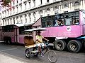 A bike taxi and large bus street scene in Cuba.jpg