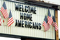 A large welcome home sign surrounded by America flags stands ready to welcome former TWA hostages back to the US DF-ST-86-03851.jpg
