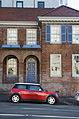 A red Mini Cooper in front a vintage brick house, Auckland - 0251.jpg