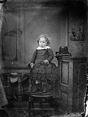 A young girl standing on a chair