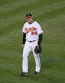 A man in a white baseball uniform with orange script across the chest and a black baseball cap walks across a grass field with a black baseball glove on his left hand