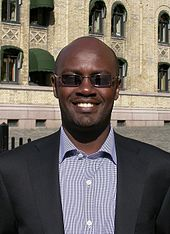 A man in a suit and sunglasses, Andrew Mwenda, smiling