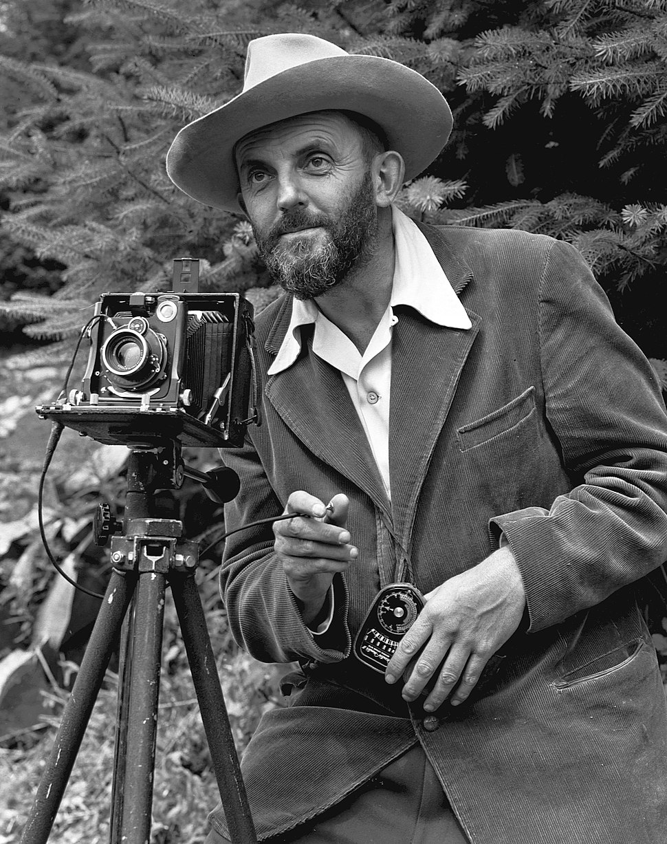 A photo of a bearded Ansel Adams with a camera on a tripod and a light meter in his hand. Adams is wearing a dark jacket and a white shirt, and the open shirt collar is spread over the lapel of his jacket. He is holding a cable release for the camera, and there is a rocky hillside behind him. The photo was taken by J. Malcolm Greany and first appeared in the 1950 Yosemite Field School Yearbook.