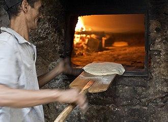 Мужчина с помощью кожуры хлеба опускает круглый диск сырого теста для лепешек в кирпичную печь.