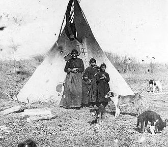 Dane-zaa - Dane-zaa (Beaver) women and children in front of their tipi, 1899