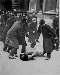 A woman is on the ground with her gloved hands over her face. A man in a top hat is holding back one police officer, while another is holding one of his gloves and stooping over the woman. In the background are several police officers and other men. Beyond them are the walls and doorway to the Parliament buildings.
