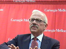 "Barr, visible from the chest up, wears a navy blue jacket with blue shirt and red and blue checkered tie, in front of a red background with the words ""Carnegie Mellon"" written on it in several places"