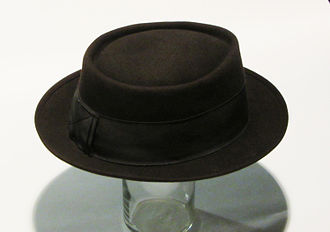 "Pork pie hat - A classic brown felt men's pork pie hat from the 1940s. Note that the ""bow"" in the back of the hat conceals a small button on a string which winds around the hat: in windy weather the button would be attached to the lapel of a jacket to keep the hat from blowing away."