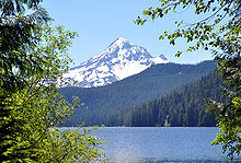 A snow-capped conical mountain rises in the distance beyond heavily forested hills at the far end of a lake.