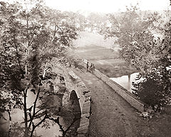A black and white photograph of a stone bridge, viewed from above. The bridge is damaged.