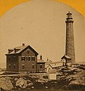 This old photograph shows a stone lighthouse built atop a rocky ledge. It is connected by a covered and enclosed walkway to a house on the left. A small white shed is visible in the foreground.