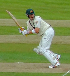 A man in cricket whites and baggy green walking towards the camera