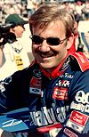 A mustached man in his early forties wearing sunglasses and blue and red racing overalls