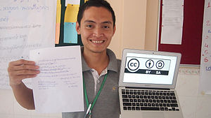 Open content - The logo on the screen in the subject's left hand is a Creative Commons license, while the paper in his right hand explains that the image is open content.