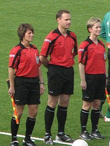 Photo de la présentation des trois arbitres en tenue (dont deux femmes) avec un ballon posé au sol.