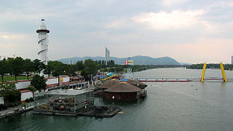Donauinsel - Copa Cagrana with lighthouse and pontoon bridge, from SE. In the background: Millennium Tower, Kahlenberg (w. antenna), Leopoldsberg (w. church) and, far out, Klosterneuburg.