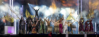 "Photograph of performance of ""Love Love Peace Peace"" at the 2016 grand final: Petra Mede and Måns Zelmerlöw perform on stage surrounded by performers dressed in costumes of past Eurovision acts"