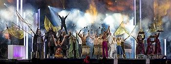 """Fotografia dell'esibizione di """"Love Love Peace Peace"""" al gran finale del 2016: Petra Mede e Måns Zelmerlöw si esibiscono sul palco circondati da artisti vestiti con i costumi delle passate esibizioni dell'Eurovision"""