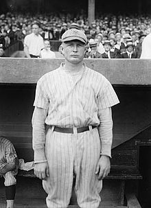 "A man in a white baseball uniform with dark pinstripes and a cap with an overlapping ""NY"" on the front stands in front of a dugout with fans in the stands behind him."