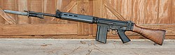 A black FN FAL battle rifle with a wooden stock