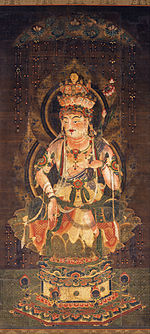 Deity embellished with ornaments seated on a pedestal.
