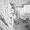 Emigrantenvrouw, een advocate uit Roemenie, bikt bakstenen temidden van een door, Bestanddeelnr 255-1204.jpg