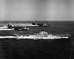 F9F-2 Panthers of VF-191 fly past USS Princeton (CV-37) off Korea, circa in May 1951 (NH 97047)