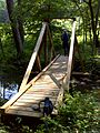 FLT M03 15.71 mi - Bridge W of US 219, 24' long, 2x6x39 deck, 2x4 side rails, 4x4 upright trusses, 6x6 stringers, 2x8 sills, 2 cables, 3.5' to drainage - panoramio.jpg