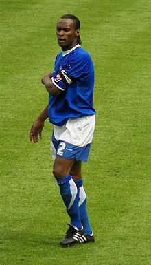 A black footballer in blue-and-white shorts, shirt and socks standing on a football pitch with his left arm across his chest