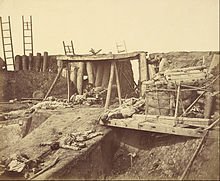 The interior of an earthen and wooden fort with dead bodies scattered around it