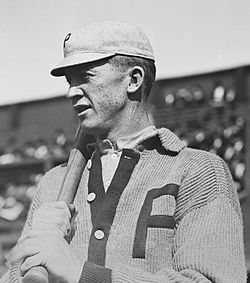 "A man wearing a sweater with the block letter ""P"" over the left breast and a light-colored baseball cap with the same ""P"" on the front holds a baseball bat over his right shoulder."
