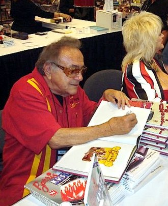 "George Barris (auto customizer) - George Barris signing autographs at the 2008 SEMA show in Las Vegas, seated next to ""Miss Hurst Shifter"" Linda Vaughn"