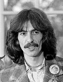 George Harrison in his early thirties, with mustache and long, dark hair