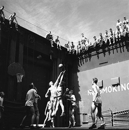 Navy pilots playing basketball in the forward elevator well, mid-1944. Jumper at left is Gerald Ford. Gerald Ford playing basketball on USS Monterey 06-1944-Darkened Larger.jpg