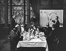 A black and white film still. A group of men sit around a dining table in the center. To the right, a man stands by and gestures at a large drawing of a dinosaur.