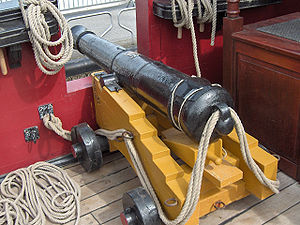 Gun laying - A naval cannon mounted on its gun carriage. The breech rope is visible.