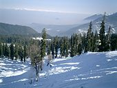 Daytime view looking down from a snowy ridge onto a mountain valley far below, lost in mist. Continuing into the far distance at right, a series of high snow-covered mountains continue the ridge. The mountains are mostly covered in evergreen forest; dappled sunlight strikes the snow cover.