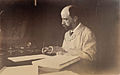 Henry Adams seated at desk in study, writing, in light coat, photograph by Marian Hooper Adams, 1883.jpg