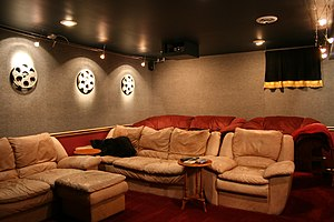 A home theater with video projector mounted in a box on the ceiling.