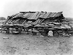 Sweat lodge - Hupa Indian underground building covered with wood plank roof and surrounded by a wall of large rocks