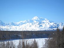 A mountain is in the background of a forest of bare trees and an icy lake.