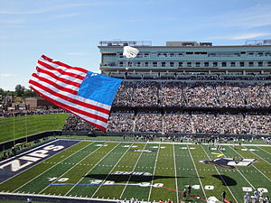 Akron Zips football - A parachuter descends with American flag in tow onto the surface of Summa Field as part of the opening day festivities.