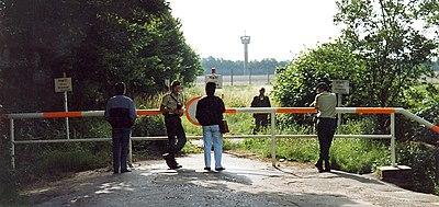 west duitse kant van de grens in lbeck twee man van de bundesgrenzschutz voor het hek en een ddr grensverkenner achter het hek