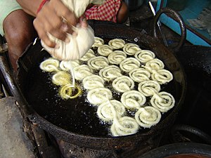 Jalebi - Jalebi batter being dropped in hot oil. Howrah, West Bengal, India