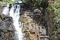 Jeune homme escaladant les parois des cascades de Tanougou 2 (Bénin).jpg