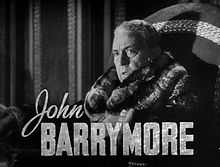 Publicity shot of a noticeably older, heavier Barrymore, wearing a fur coat; side on, facing slightly to his left