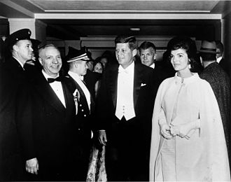 White tie - President John F. Kennedy and First Lady Jacqueline Kennedy, wearing a gown designed by Ethel Franken of Bergdorf Goodman, arrive at the D.C. Armory in Washington D.C. for an inaugural ball held on the evening of Inauguration Day, January 20, 1961.